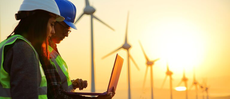 people - 2 workers looking at laptop in front of windmills at sunset